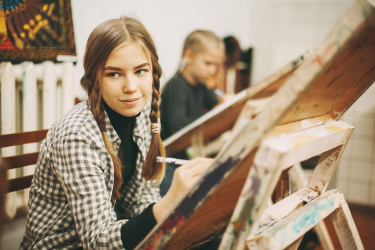 Beautiful teenage girl at art school painting on easel, creativity concept,