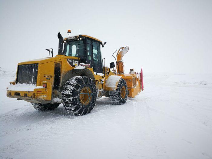 Snowplow On Field Against Clear Sky