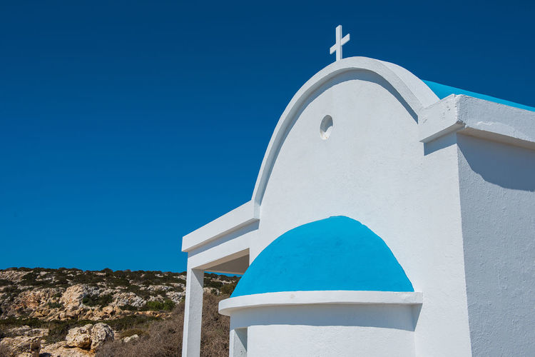 Traditional Greek white church with a blue roof on the seaside. Agioi Anargyroi orthodox monastery, Cyprus Agioi Anargiroi Chapel Church Coastline Cross Cyprus Orthodox Church Architecture Blue Blue Sky Built Structure Coast Day Nature No People Orthodox Outdoors Place Of Worship Religion Religions Sea Sky Spirituality Sunshine Whitewashed