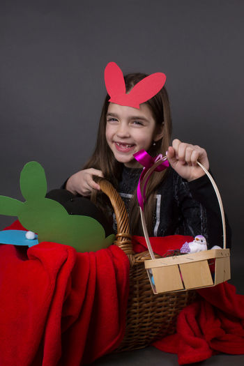 Portrait of smiling girl with costume rabbit ears sitting in basket against gray background