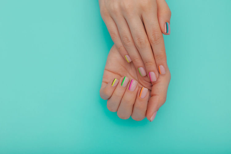 Close-up of woman hand against blue background