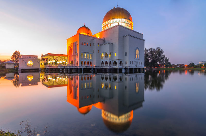 Reflection of as-salam mosque in water during sunrise