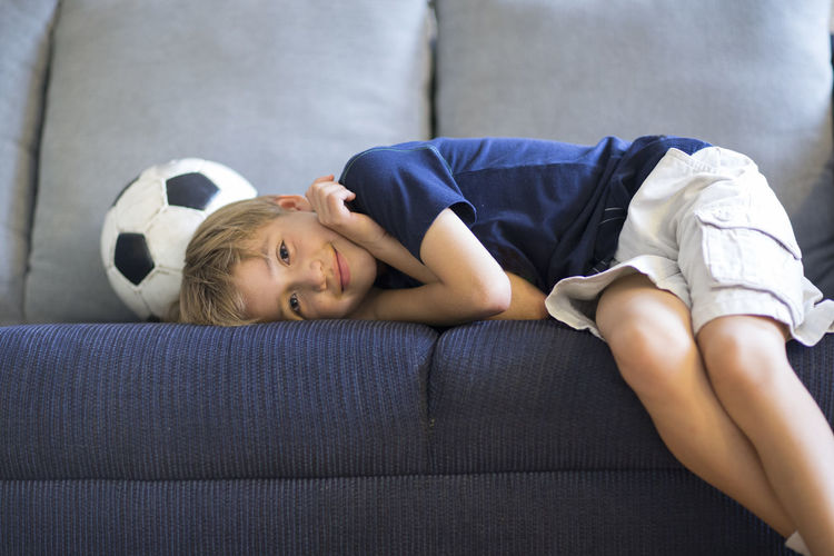 Portrait Of Boy With Soccer Ball Lying On Sofa At Home