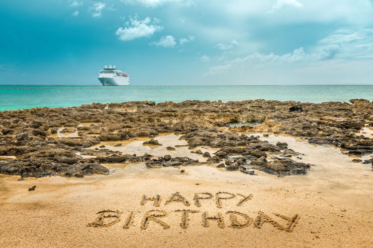 Hand written happy birthday on the sandy beach by the ocean with a cruise ship in the background