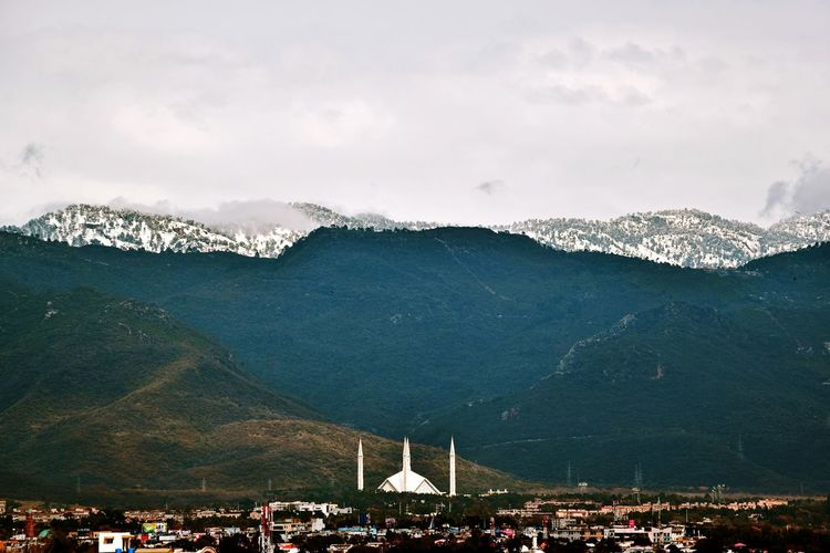 Scenic view of mountains by shah faisal masjid against sky