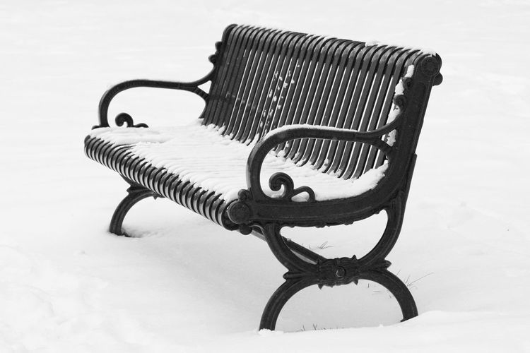 Park Bench Covered With Snow During Winter