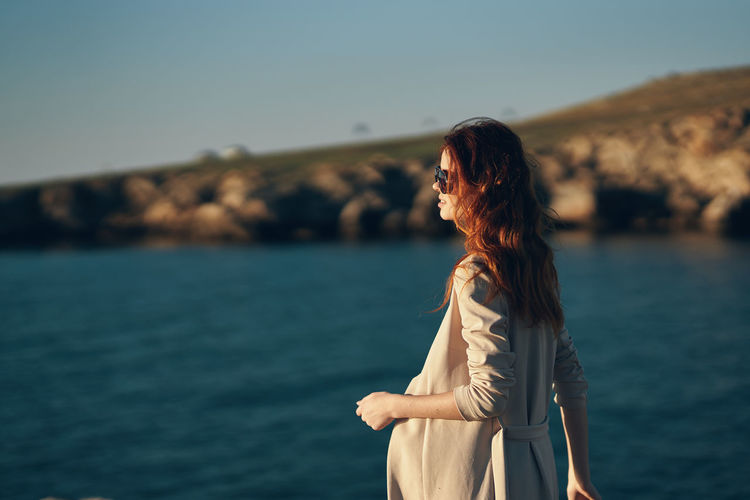 Woman standing near sea against sky