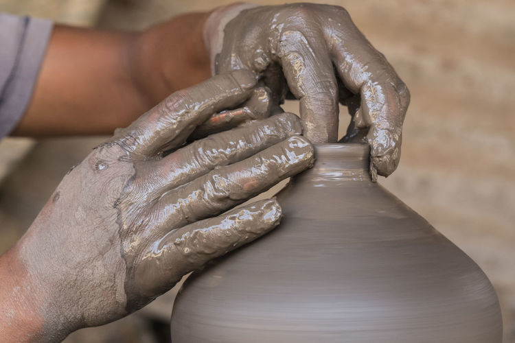 Hands of a potter. Potter making ceramic pot on the wheel. Bhaktapur Nepal. Human Hand Hand Human Body Part Occupation Working Focus On Foreground One Person Indoors  Art And Craft Creativity Close-up Skill  Holding Craft Pottery Molding A Shape Finger Real People Pot Workshop Fingers Vase Wet Ceramics Spinning Around