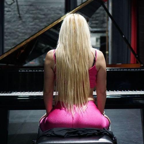 Rear view of woman sitting with piano
