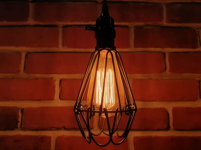 Close-up of illuminated light bulb against brick wall