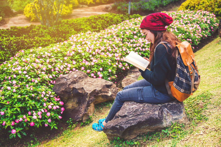 Woman reading book while sitting on stone