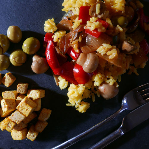Close-up Food Food And Drink Freshness Healthy Eating Indoors  Still Life Table Vegetable vegan paella with grilled tofu cubes and olives At Table Fork Knife Plate Black Background Vegan Vegetarian Tofu Cubes Healthy Food Green Olives Paellas Cutlery View From Above Slate