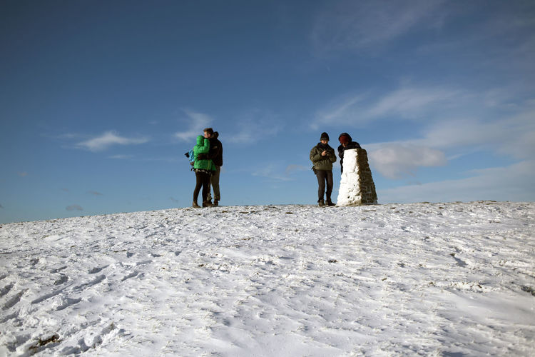 Rear view of people on snow covered land against sky