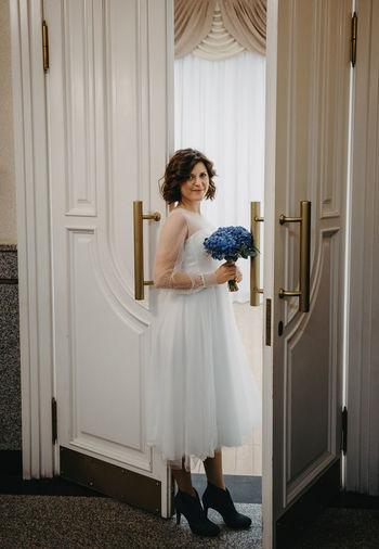 Woman standing against white door