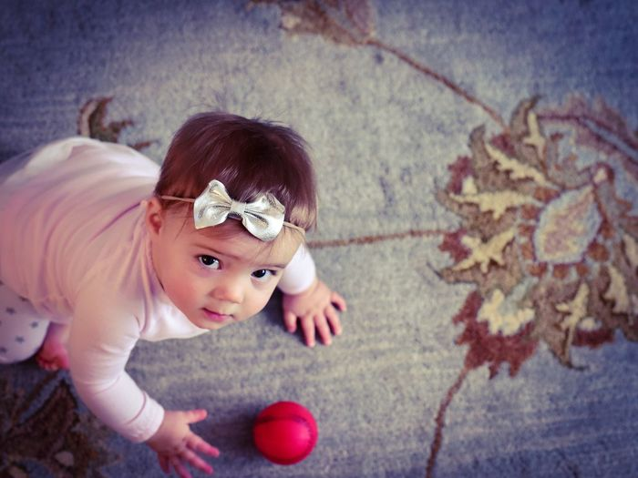 High angle portrait of cute baby girl playing with ball on carpet