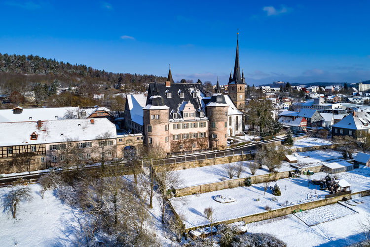 Air view of Ahorn castle in Coburg, Bavaria, Germany Ahorn, Air, Air View, Architecture, Bavarian, Birds Eye Perspective, Building, Castle, Cities, Coburg, Culture, Destinations, Europe, European, Germany, House, Palace, Rural, Snow, Street, Travel, Winter Architecture Beauty In Nature Blue Building Exterior Built Structure Cold Temperature Day Frozen Mountain Nature No People Outdoors Sky Snow Snowdrift Tree Weather Winter