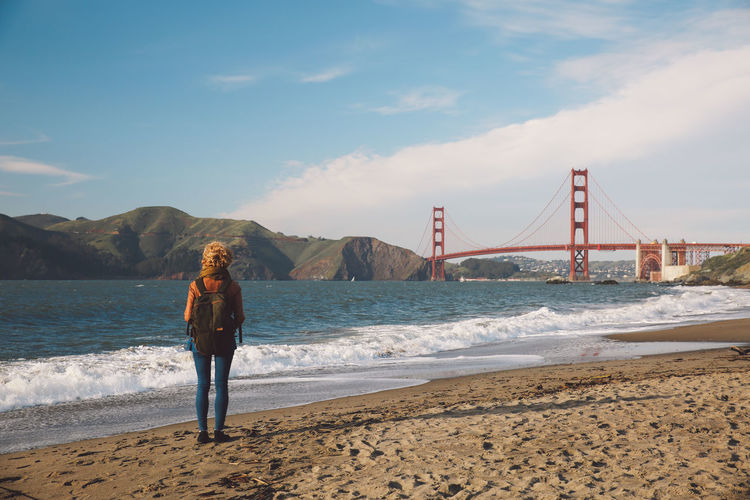 Rear view of woman standing on shore with golden gate bridge in background
