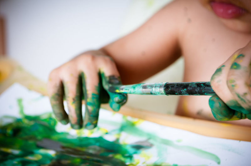 Midsection of child holding paintbrush with watercolor paints