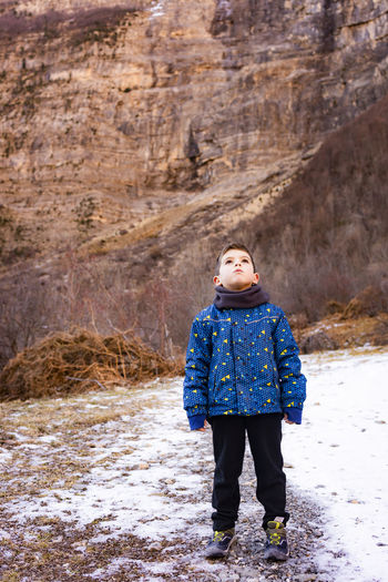 Cute boy standing on snowy field against mountains
