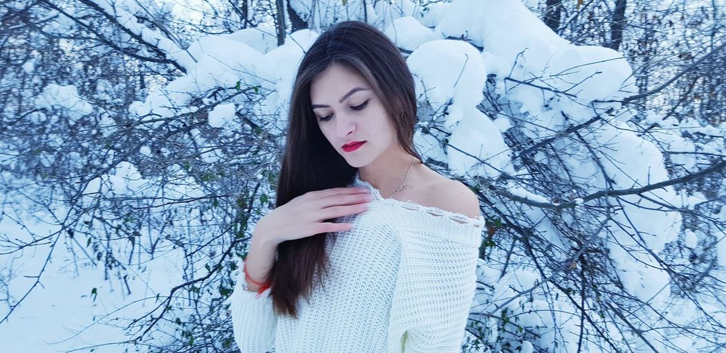 Beautiful young woman standing against snow covered bare tree in forest