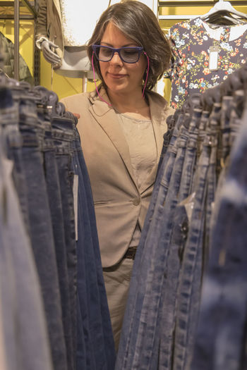 Woman Shopping Jeans In Store