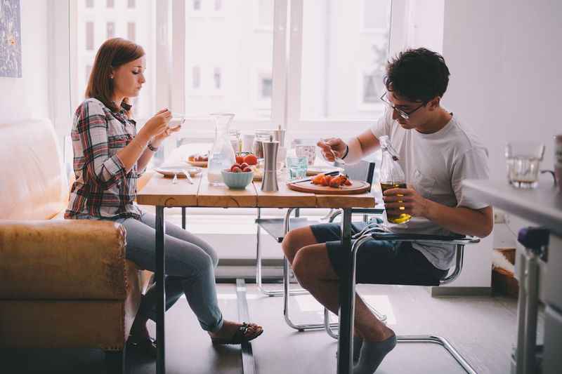 Man And Woman Eating Food On Table