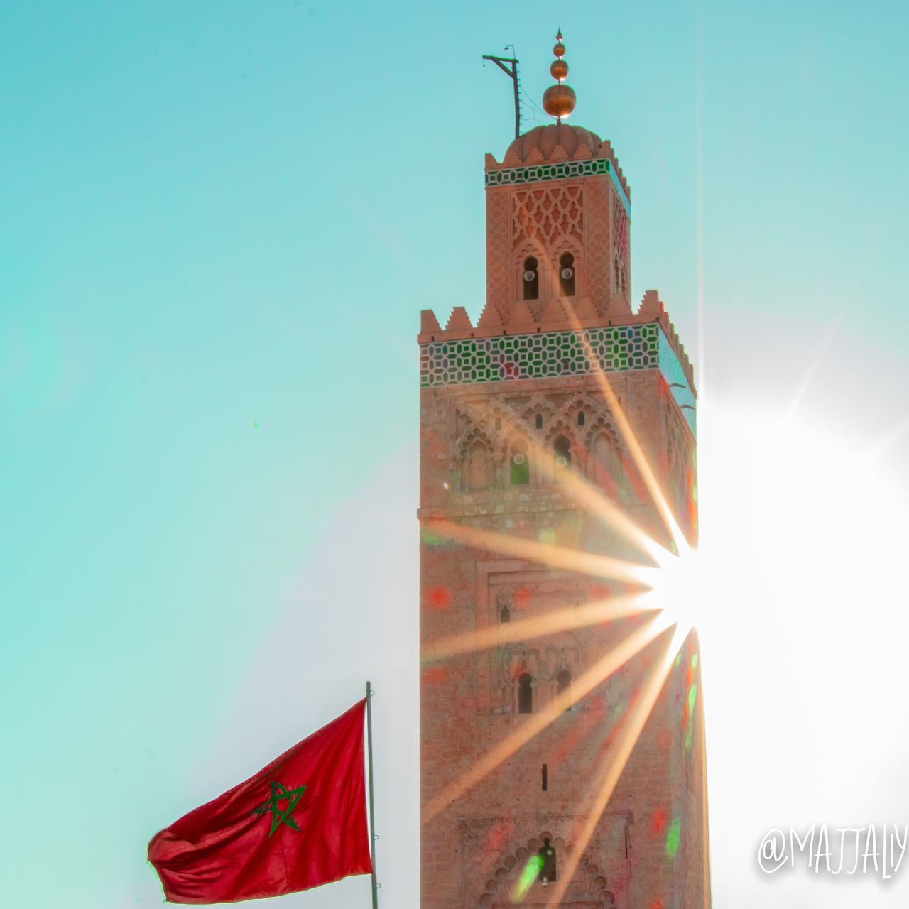 built structure, sky, architecture, building exterior, building, nature, no people, tower, low angle view, clear sky, sunlight, lens flare, flag, sun, day, religion, travel destinations, city, tourism, outdoors