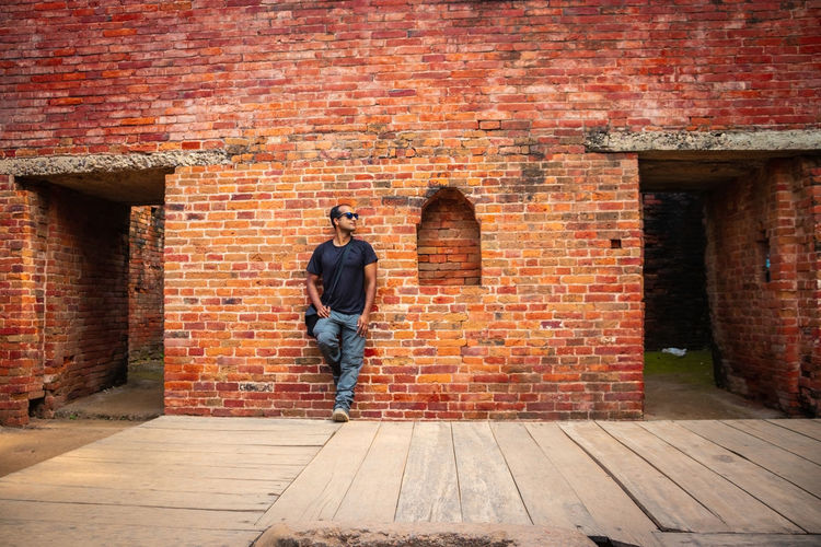 Man standing against brick wall