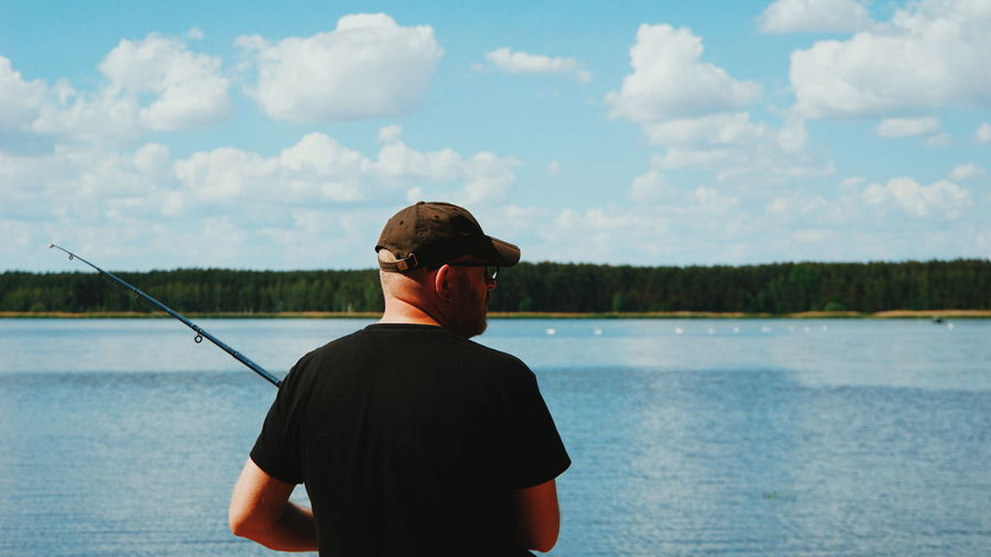 Rear view of man holding fishing rod while standing by lake