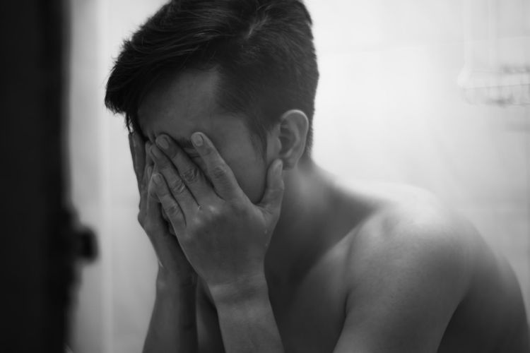 Close-up of stressed man covering face with hands