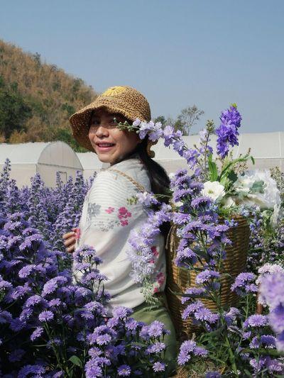 Portrait of smiling woman with purple flowers against plants
