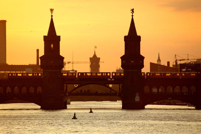 Silhouette Of Bridge Over River During Sunset