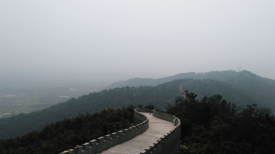 Scenic View Of The Great Wall Of China Against Cloudy Sky