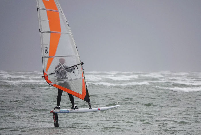 A professional windsurfer testing the latest hydrofoiling board off Hayling Island in Hampshire, UK. Hayling Island  Windfoil Windfoiling Adventure Aquatic Sport Coast England Hampshire  Hants Horizon Over Water Hydrofoil Leisure Activity Motion Nature Outdoors Real People Sailboard Sailboarding Sea Speed Sport Water Watersports Windsurf Windsurfing