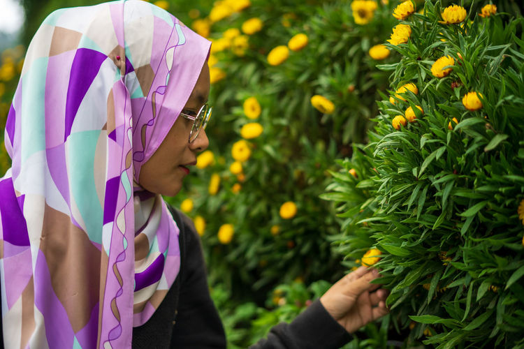 Side view of woman looking at plants