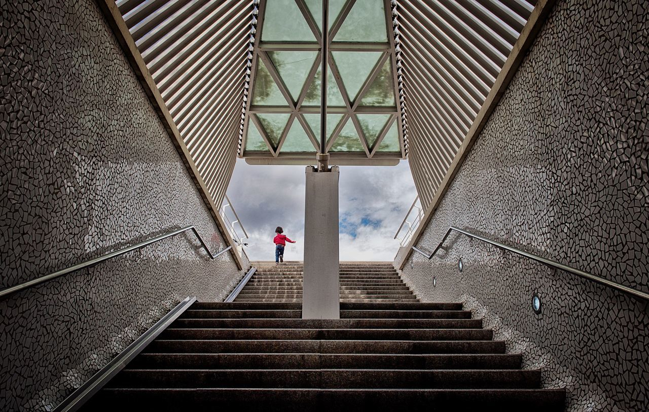 Low Angle View Of Child Walking On Steps Against Sky