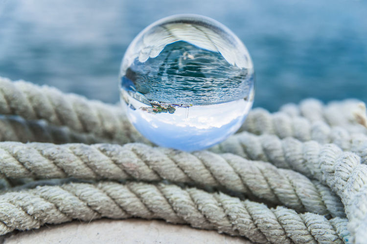 Close-up of crystal ball on rope at harbor