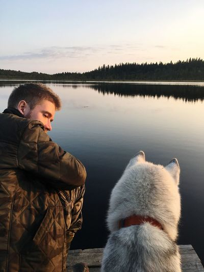 Rear View Of Man With Dog By Lake Against Sky