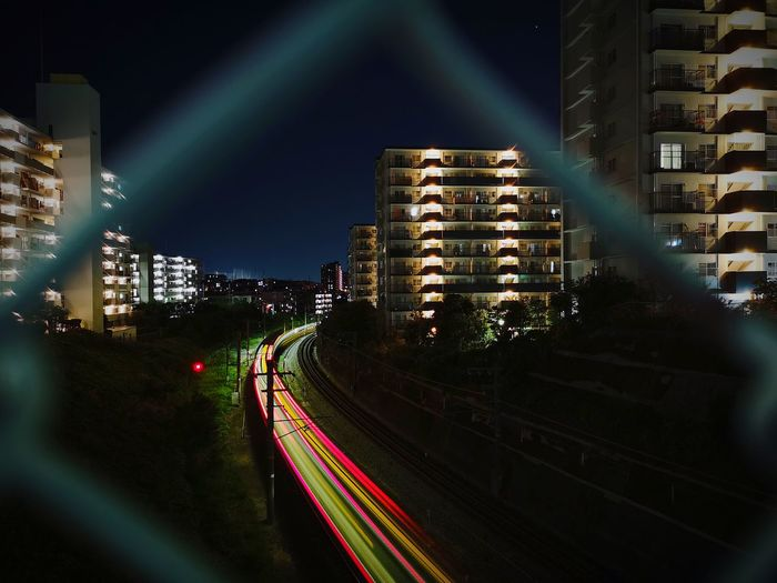 Light trails on road amidst buildings seen through chainlink fence