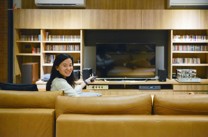 Asian woman watching blank screen TV in living room at night Book Bookshelf Cabinet Casual Clothing Comfortable Day Home Interior Home Showcase Interior Indoors  Leisure Activity Lifestyles Living Room Looking At Camera Night One Person People Portrait Real People Relaxation Shelf Sitting Sofa Technology Tv Watching Young Adult Young Women
