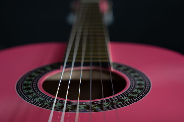 close up from a guitar with a selective focus on the fretboard. Music String Instrument Musical Instrument Studio Shot Arts Culture And Entertainment Guitar Indoors  Musical Equipment Close-up Musical Instrument String Acoustic Guitar String Black Background Single Object Selective Focus Still Life Wood - Material Pink Color Playing Wallpaper Fretboard Abstract Backgrounds