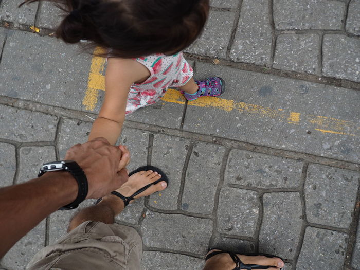 High Angle View Of Girl  Holding Hands With Man On Cobblestone Streets
