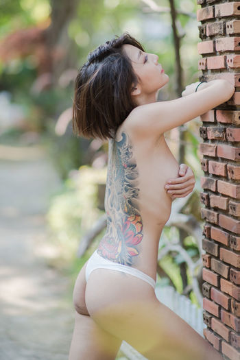 Side view of shirtless female model standing by brick wall