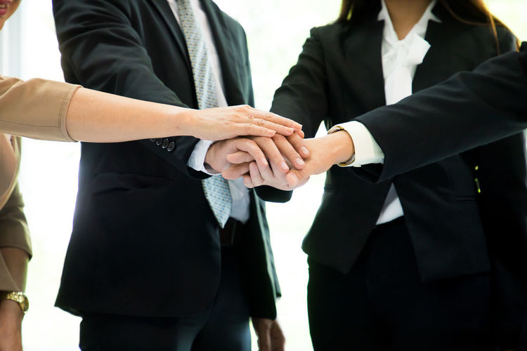 Midsection of business colleagues stacking hands