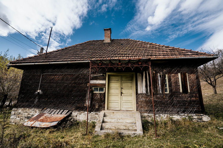 Exterior of old house on field against sky