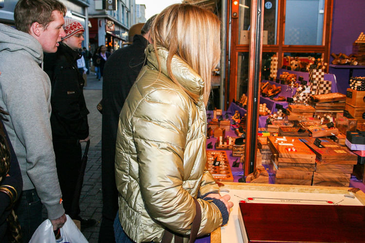 A blonde haired woman in a shiny gold winter coat shops at a Christmas Market stall in Bristol Adult Alone Blooming Christmas Cold Day Gifts Gold Gold Coat Hair Hidden Market Market Stall Outdoors People Presents Real People Retail  Shopping Water Winter Xmas Market Young Young Women EyeEmNewHere