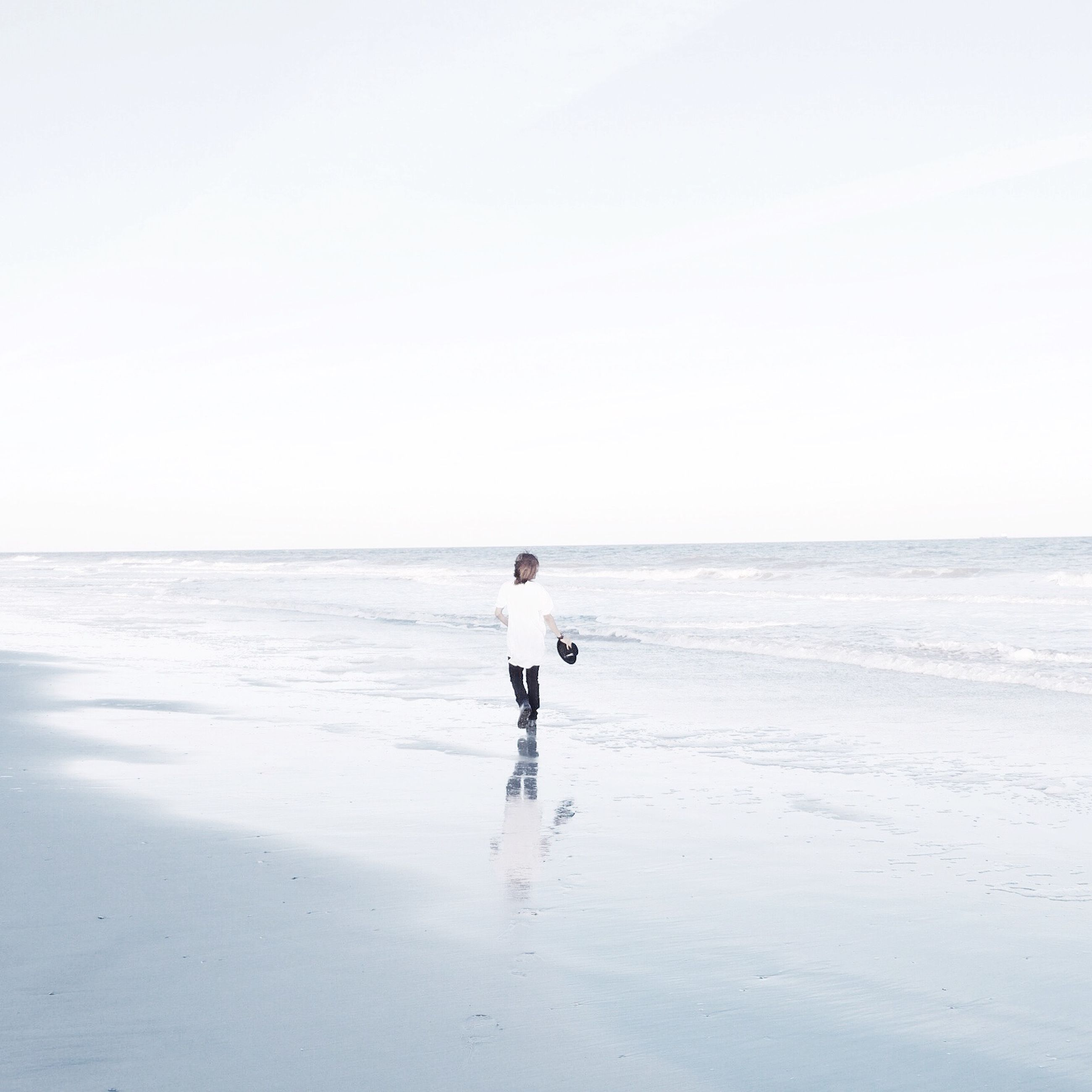 beach, sea, horizon over water, water, shore, full length, sand, leisure activity, clear sky, walking, lifestyles, rear view, copy space, tranquil scene, standing, tranquility, scenics, wave