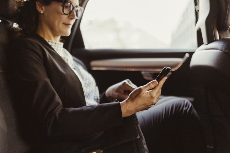 Midsection of man using mobile phone while sitting in car