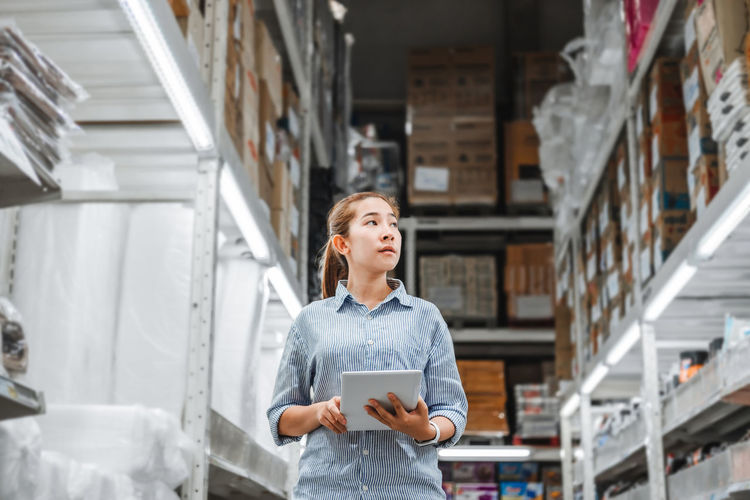 Side view of woman holding digital tablet while standing in warehouse