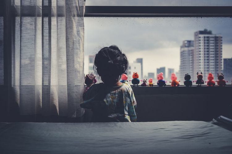 Rear view of girl playing with toys on window sill at home